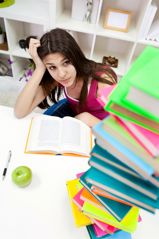 worried student girl looking in books